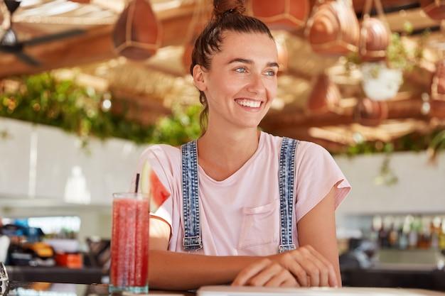 Portret van schattig blauwogig vrouwelijk model met haarknoop draagt overall, geniet van het drinken van fruit smoothie, kijkt gelukkig ergens terwijl zit in gezellig restaurant. mooie tiener in coffeeshop