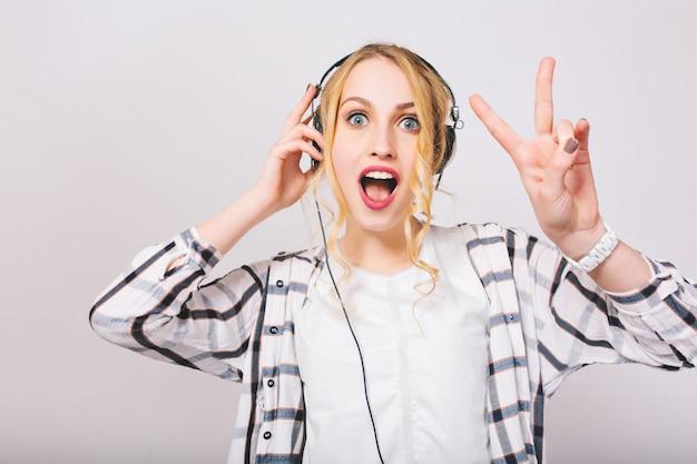 Portret van schattig blond krullend meisje in koptelefoon luisteren muziek met verbaasd gezicht en dansen. charmante dame met blauwe ogen en open mond toont vredesteken met plezier en geniet van favoriete liedje.