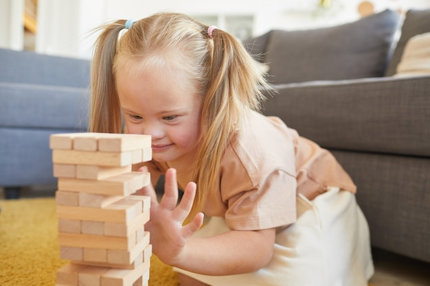 Portret van schattig blond meisje met syndroom van down spelen bordspellen stapelen houtblokken zittend op de vloer thuis, kopieer ruimte