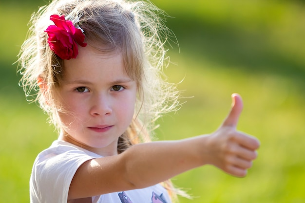 Portret van schattig klein blond ernstig meisje in wit t-shirt met rode roos