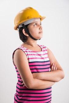 Portret van schattig klein indisch meisje in gele helm met papierrol, staande geïsoleerd op witte achtergrond
