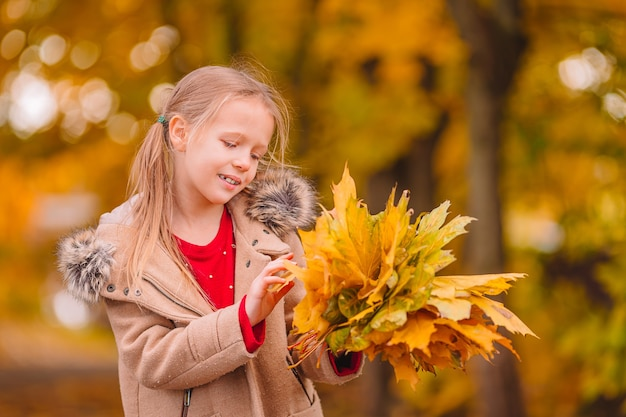 Portret van schattig klein meisje buiten op mooie warme dag met gele bladeren in de herfst