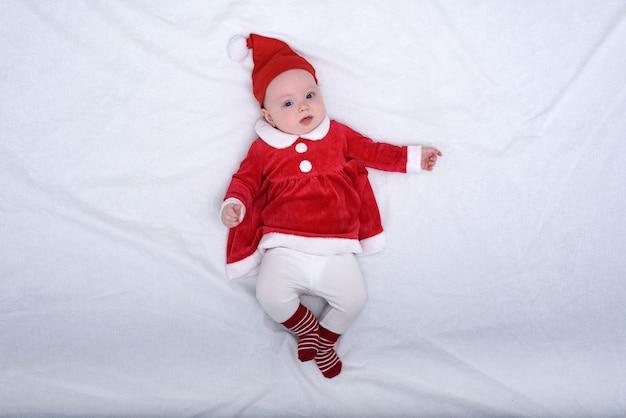 Portret van schattig klein meisje in een kerstmuts en een rode jurk.