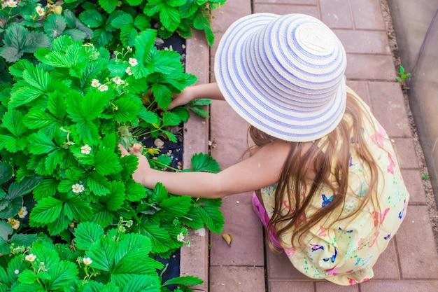 Portret van schattig klein meisje in hoed zitten in de tuin