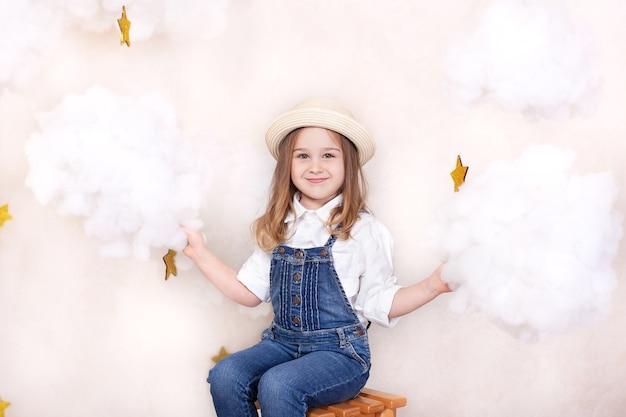 Portret van schattig klein meisje in strooien hoed. glimlachend kind vliegt in de lucht met wolken en sterren.