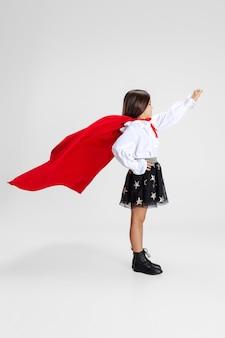 Portret van schattig klein meisje kind in rode mantel geïsoleerd over witte studio achtergrond superheld