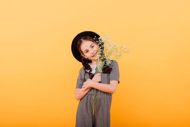 Portret van schattig klein meisje met bloemboeket in de studio op gele achtergrond. felicitatie, lente of prettige vakantie concept. kopieer ruimte voor tekst