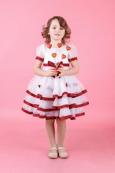 Portret van schattig klein meisje permanent in witte jurk met donuts of glazen hart op het roze in de studio