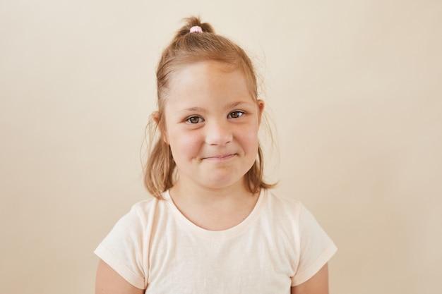 Portret van schattig klein meisje tegen de witte achtergrond
