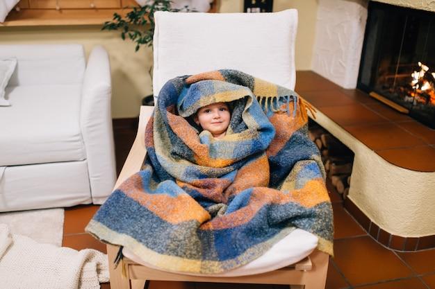 Portret van schattig klein meisje zit in haar kamer gewikkeld in een sprei zit op een fauteuil