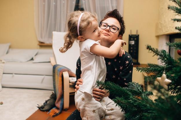 Portret van schattig klein meisje zit in haar kamer zit met mooie moeder