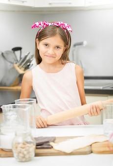 Portret van schattig lachend meisje met deegroller deeg maken
