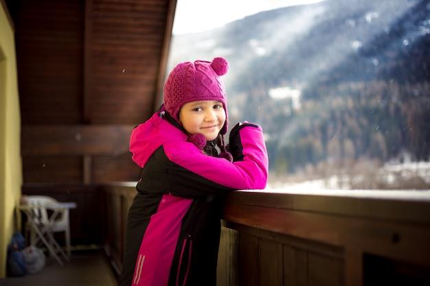Portret van schattig lachend meisje poseren op balkon tegen besneeuwde alpen