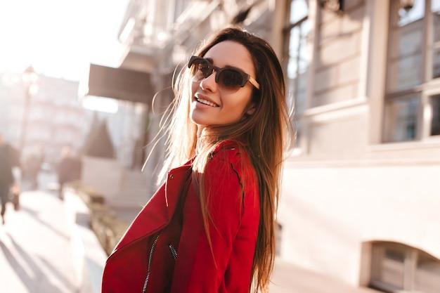 Portret van schattig langharig meisje in zonnebril over schouder kijken op vervagen stadsruimte