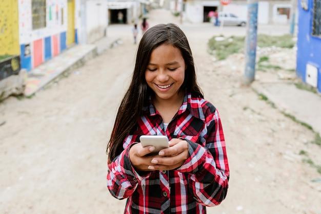 Portret van schattig latino meisje met behulp van de mobiele telefoon in de sloppenwijk. jeugd concept.