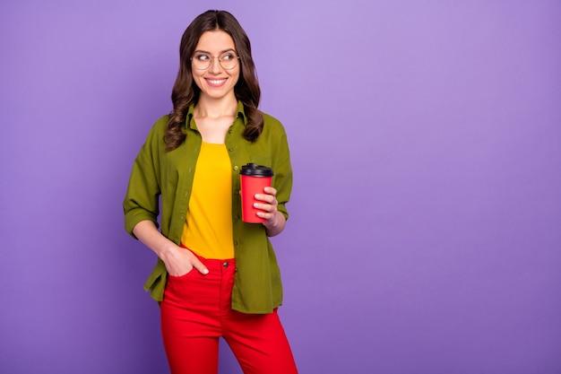 Portret van schattig leuk mooi tevreden meisje geniet van de zomer vrije tijd houd warme cacao drank afhaalmaaltijden kop look copyspace draag casual stijl kleding geïsoleerd over violette kleur achtergrond
