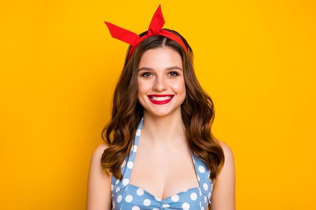 Portret van schattig meisje dragen polka-dot jurk singlet hoofdband geïsoleerd over gele muur