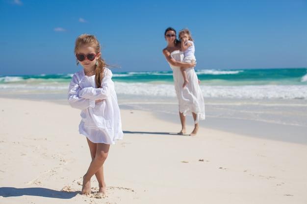 Portret van schattig meisje en haar moeder met kleine zusje in het tropische strand