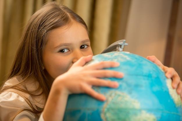 Portret van schattig meisje hand in hand op earth globe