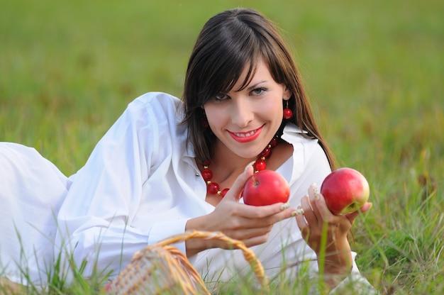 Portret van schattig meisje in wit overhemd en rode ketting ligt op gras en appels in handen houdt