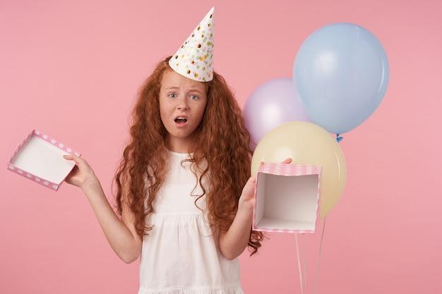 Portret van schattig meisje met foxy krullend haar in elegante jurk en verjaardag pet viert vakantie, wordt teleurgesteld om een leeg verjaardagscadeau te krijgen, geïsoleerd op roze studio achtergrond