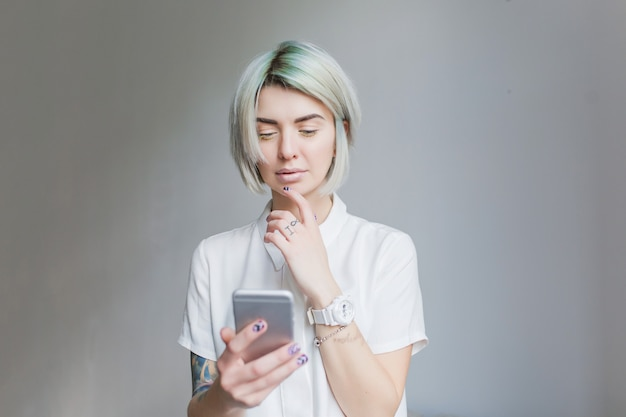 Portret van schattig meisje met grijze korte haarstijl staande op een grijze achtergrond. ze draagt een witte jurk en lichte make-up, houdt de telefoon vast.