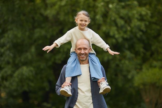 Portret van schattig meisje zittend op vaders schouders en plezier terwijl u geniet van wandelen in het park