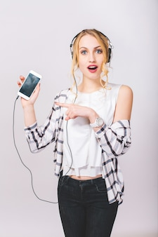 Portret van schattig mooi blond meisje met verbaasd gezicht poseren, kijken. gelukkig tevreden vrouw die haar smartphone toont. stijlvolle outfit dragen.