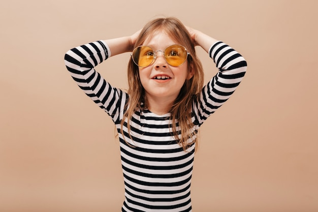 Portret van schattig mooi meisje in ronde trendy bril close-up en gestripte jurk hand in hand en glimlachen