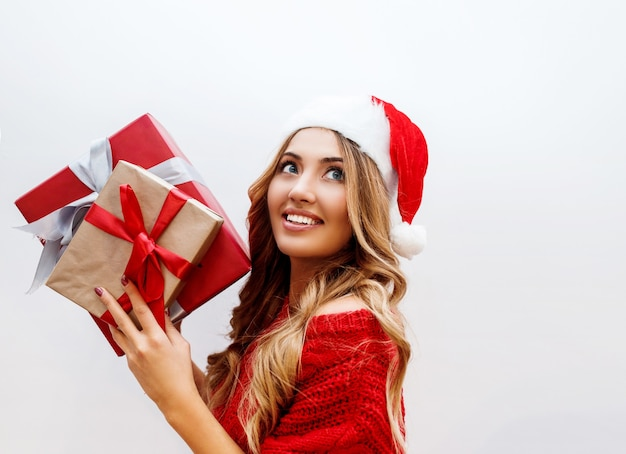 Portret van schattig onbezorgd meisje met glanzende golvende blonde haren poseren met geschenkdoos close-up. het dragen van rode kerstmaskerade hoed en trui.