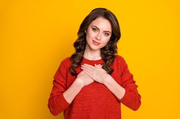 Portret van schattig schattig meisje met handpalmen op de borst, voel dankbare vrienden, familie draagt een trui die geïsoleerd is over een felle kleurachtergrond