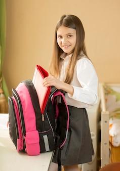 Portret van schattig schoolmeisje dat haar tas in de slaapkamer inpakt