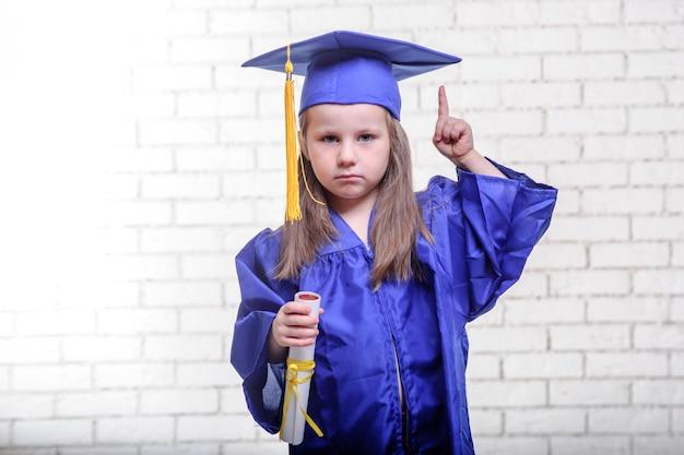 Portret van schattig schoolmeisje met afstuderen hoed in de klas