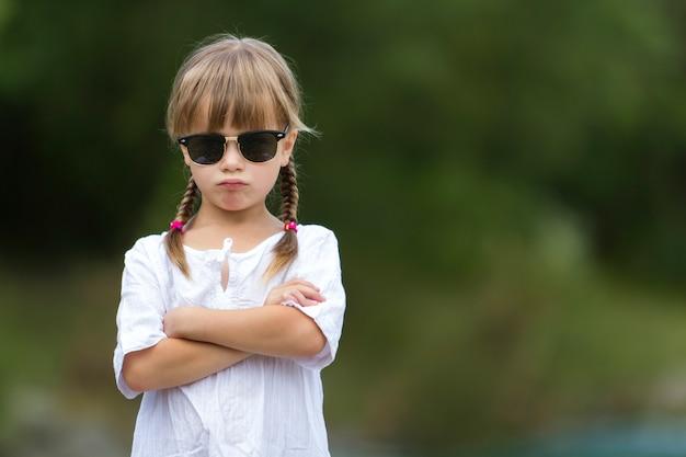 Portret van schattig vrij grappig cool zelfverzekerd modieus humeurig jong blond preschool meisje met blonde vlechten in witte jurk