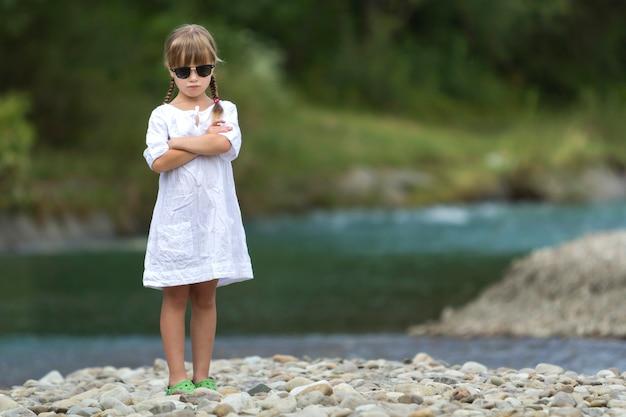 Portret van schattig vrij grappig jong meisje met blonde vlechten in witte jurk en donkere zonnebril.