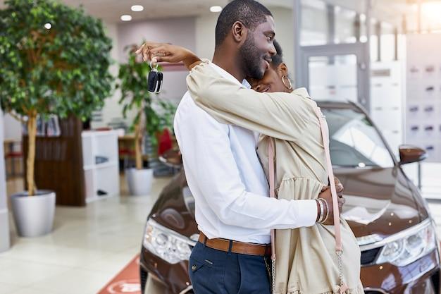 Portret van schattige afrikaanse echtpaar knuffelen elkaar in auto showroom