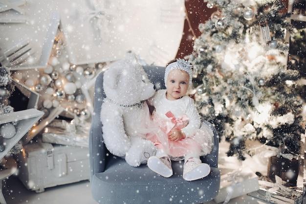 Portret van schattige baby in prachtige vooruitzichten zittend op een fauteuil met witte teddybeer en glimlachend in de camera. kerst versierd interieur en verlichte boom.