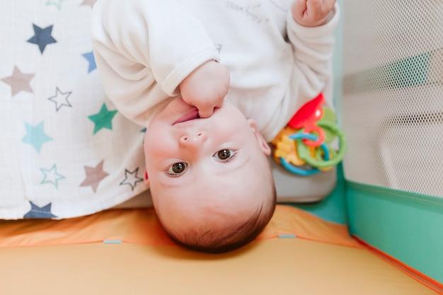 Portret van schattige babyjongen in een wieg die nieuwsgierig de camera bekijkt