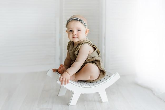 Portret van schattige babymeisje poseren op vintage bankje