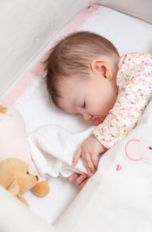 Portret van schattige babymeisje slapen in een kinderbedje met fopspeen en knuffel