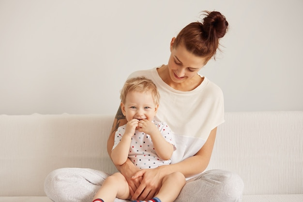 Portret van schattige blonde blauwogige babyjongen die met een gelukkige glimlach kijkt