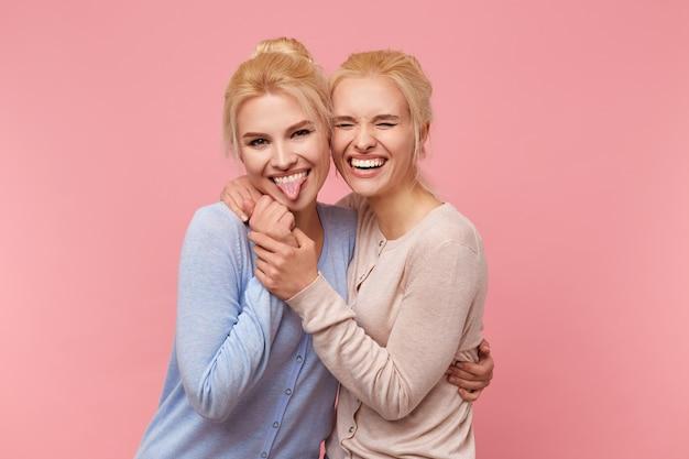 Portret van schattige blonde tweeling, omhelsd en handen vastgehouden, met plezier en breed glimlachend in de camera, staat over roze achtergrond.