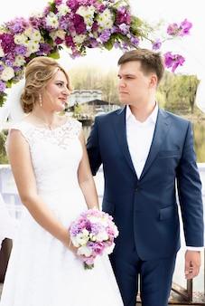 Portret van schattige bruid en bruidegom die elkaar aankijken tijdens de huwelijksceremonie