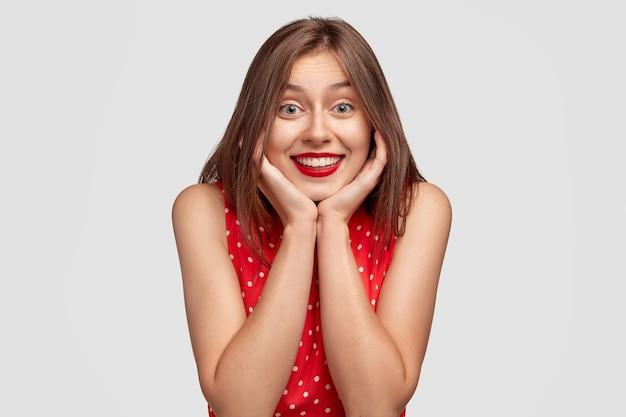 Portret van schattige brunette jonge vrouw poseren tegen de witte muur