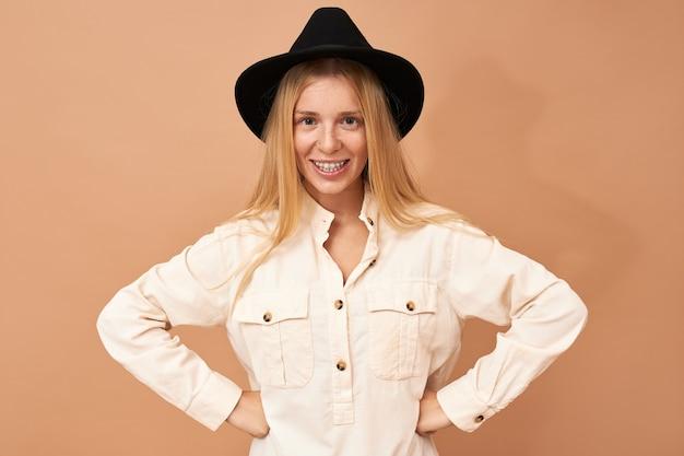 Portret van schattige charmante jonge blanke vrouw met zwarte hoed poseren geïsoleerd in zelfverzekerde vastberaden houding met handen op haar middel, breed glimlachend