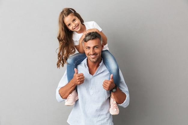 Portret van schattige familie, dochter glimlachend en zittend op de nek van haar vader, geïsoleerd over grijs