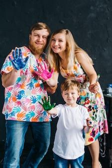 Portret van schattige gelukkige familie schilderen en plezier maken. ze tonen hun handen geschilderd in felle kleuren. we blijven thuis, hebben lol en tekenen.