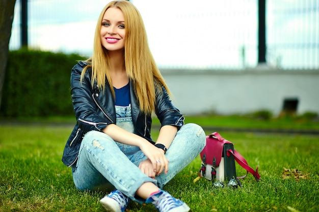 Portret van schattige grappige blonde moderne sexy stedelijke jonge stijlvolle lachende vrouw meisje model in heldere moderne doek buiten zitten in het park op het groene gras in jeans met roze tas