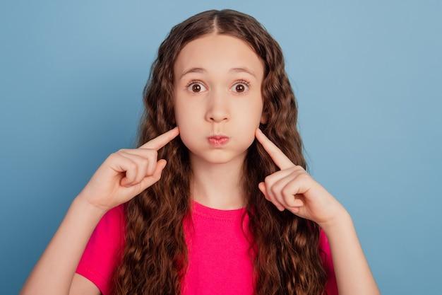 Portret van schattige grappige droom klein meisje blaast wangen op met vingers op blauwe achtergrond
