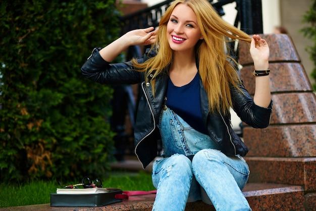 Portret van schattige grappige moderne sexy stedelijke jonge stijlvolle lachende vrouw meisje model in heldere moderne doek buiten zitten in het park in spijkerbroek op een bankje